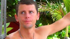 El hombre joven que se sienta en el oscilación de la cuerda en la selva y piensa en vida almacen de video