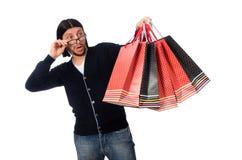 El hombre joven que sostiene las bolsas de plástico aisladas en blanco Fotografía de archivo libre de regalías