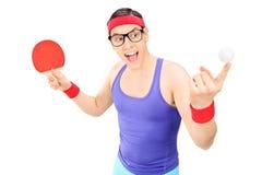 El hombre joven que sostiene una bola y un ping-pong golpean Foto de archivo libre de regalías
