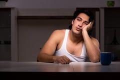 El hombre joven que sufre en casa noche fotos de archivo