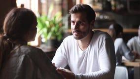 El hombre joven que tiene conversación con la mujer se sienta en la tabla del café metrajes