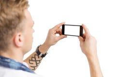 El hombre joven que toma la foto con el teléfono móvil, aislado en el fondo blanco para usted posee imagen Imagen de archivo libre de regalías