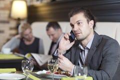 El hombre joven que trabaja con el ordenador portátil utiliza el teléfono. Sus colegas conducen la conversación imagenes de archivo