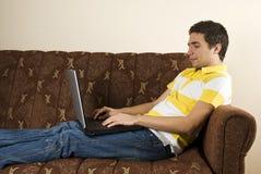 El hombre joven que trabaja en la computadora portátil y se sienta en el sofá Fotografía de archivo libre de regalías