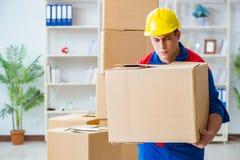El hombre joven que trabaja en servicios de la relocalización con las cajas Fotografía de archivo libre de regalías