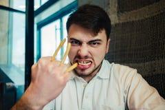 El hombre joven que usa a Hamming fríe en la tenencia del restaurante de los alimentos de preparación rápida Imagenes de archivo