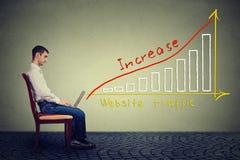El hombre joven que usa un ordenador portátil tiene un plan para aumentar tráfico del sitio web Foto de archivo