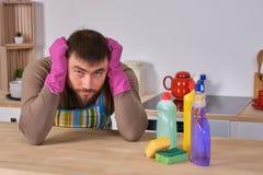 El hombre joven quiso ayudar a su esposa en housecleaning, pero él no conoce qué hacer con todos los detergentes imágenes de archivo libres de regalías