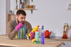 El hombre joven quiso ayudar a su esposa en housecleaning, pero él no conoce qué hacer con todos los detergentes fotografía de archivo libre de regalías