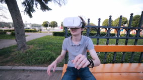 El hombre joven quita 360 vidrios de VR, emocionados jugando a los juegos de VR, impresionados mirando 360 vídeos de la realidad  almacen de video