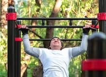El hombre joven realiza los deportes ejercita levanta en la barra Entrenamiento en la calle para desarrollar la fuerza de los m?s imagen de archivo