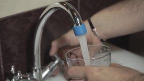 El hombre joven recolecta un vidrio de agua del golpecito almacen de video