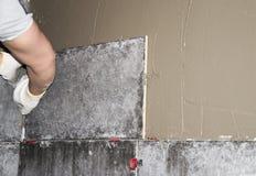 El hombre joven repara, pega las tejas grises del granito, asemejándose al hormigón, en la pared una pared cubierta con el cement fotos de archivo