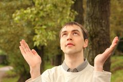 El hombre joven ruega al aire libre en verano Fotografía de archivo