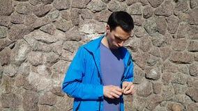 El hombre joven saca un paquete de goma y comienza a masticar la goma almacen de metraje de vídeo