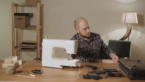 El hombre joven saca una caja de hilos y de agujas Trabajo como sastre y usar una máquina de coser en un estudio de la materia te metrajes