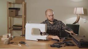El hombre joven saca una caja de hilos y de agujas Trabajo como sastre y usar una máquina de coser en un estudio de la materia te almacen de video