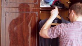 El hombre joven saca una camisa del armario almacen de metraje de vídeo
