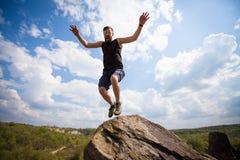 El hombre joven salta desde arriba de la roca Imagen de archivo libre de regalías