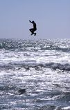 El hombre joven salta en agua Imagenes de archivo