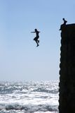 El hombre joven salta en agua. Foto de archivo