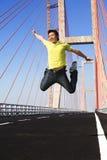 El hombre joven salta muy arriba en área del puente Imagenes de archivo