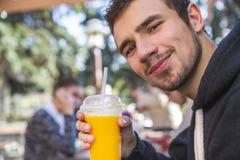 El hombre joven satisfecho está mirando la cámara con una sonrisa en su cara Él está sosteniendo el zumo de fruta en su mano dere fotografía de archivo libre de regalías