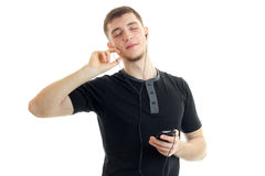 El hombre joven se cerró los ojos y escucha la música con los auriculares con el teléfono Foto de archivo