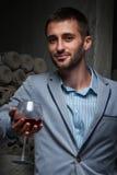 El hombre joven se coloca con el vidrio de vino Imagen de archivo libre de regalías