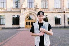 El hombre joven se coloca en la entrada a su universidad y sostiene un cuaderno en sus manos Imagenes de archivo
