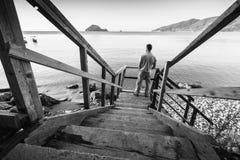 El hombre joven se coloca en la escalera de madera costera Fotografía de archivo libre de regalías