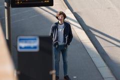 El hombre joven se coloca en una parada de autob?s fotos de archivo