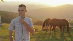 El hombre joven se está colocando en el campo cerca de las montañas Detrás de él que pasta caballos Puesta del sol Cámara lenta almacen de video