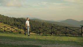El hombre joven se está colocando en el campo cerca de las montañas Detrás de él que pasta caballos Puesta del sol Hombre lento d almacen de metraje de vídeo