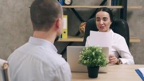El hombre joven se está entrevistando con para el trabajo en el encargado de sexo femenino en oficina
