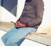 El hombre joven se está sentando con un smartphone Imagen de archivo