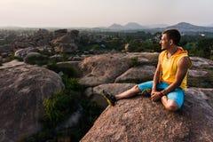 El hombre joven se está sentando en la montaña con hermosa vista y está mirando adelante Fotos de archivo