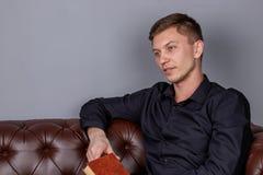El hombre joven se est? sentando en un sof? de cuero y est? leyendo un libro foto de archivo libre de regalías