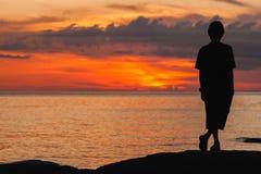 El hombre joven se levanta y mira la playa Imagen de archivo libre de regalías