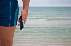 El hombre joven se opone a los controles del horizonte del agua de las ondas de arena de la playa de la orilla de mar en su teléf Foto de archivo libre de regalías