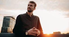 El hombre joven se opone y sonríe en el tejado de la casa contra el fondo de rascacielos y de la puesta del sol Imágenes de archivo libres de regalías