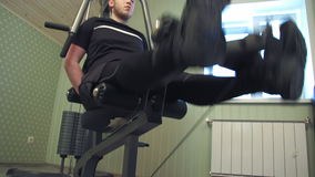 El hombre joven se resuelve en su equipo casero del gimnasio para ejercitar sus músculos de la pierna metrajes