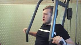 El hombre joven se resuelve en su equipo casero del gimnasio para ejercitar sus músculos del pecho almacen de video