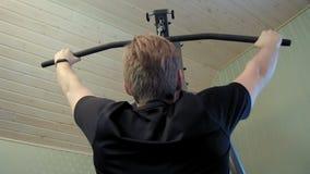 El hombre joven se resuelve en su equipo casero del gimnasio para ejercitar sus músculos del shouloder almacen de video