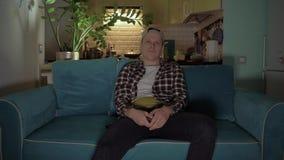 El hombre joven se sentó en el sofá, colocándose en el fondo de la cocina, y dio vuelta en la TV remota 4K metrajes