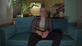 El hombre joven se sentó en el sofá, colocándose en el fondo de la cocina, y dio vuelta en la TV remota 4K almacen de metraje de vídeo