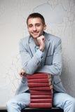 El hombre joven se sienta con los libros Foto de archivo libre de regalías