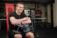 El hombre joven se sienta después de entrenamiento en gimnasio Fotos de archivo