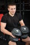 El hombre joven se sienta después de entrenamiento en gimnasio Imagenes de archivo