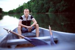 El hombre joven se sienta en el barco Imagen de archivo